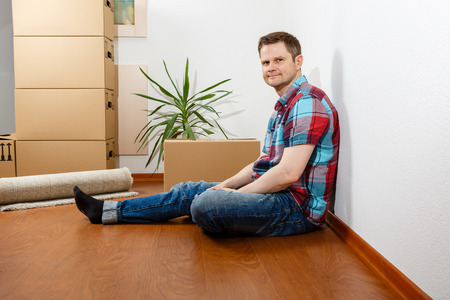 Man sitting leaning against a white wall and relaxing Standard-Bild