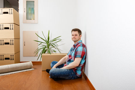 Man sitting leaning against a white wall and relaxing Standard-Bild - 122187399