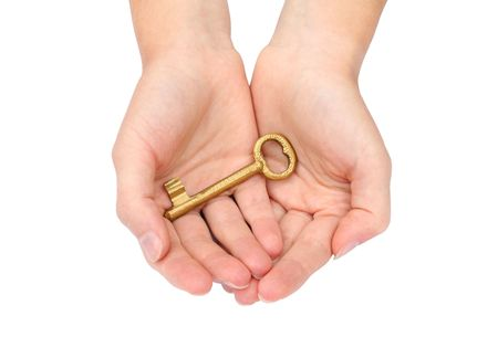 Hand holding a gold key