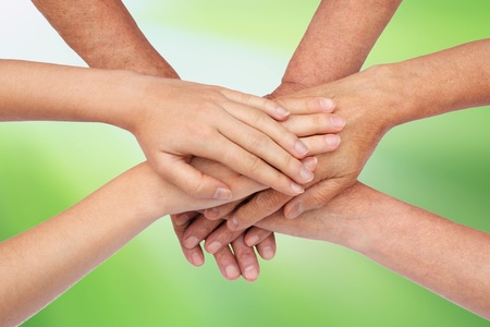 Hands on top of each other green Stock Photo