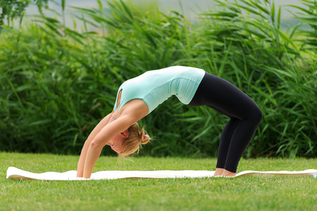 slicked back hair: Young woman doing Bridge Pose in Yoga