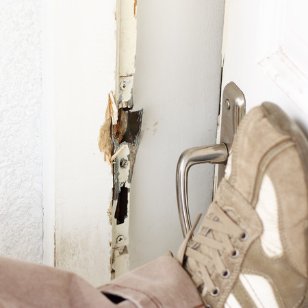 law breaker: Burglar breaking into a house with foot Stock Photo
