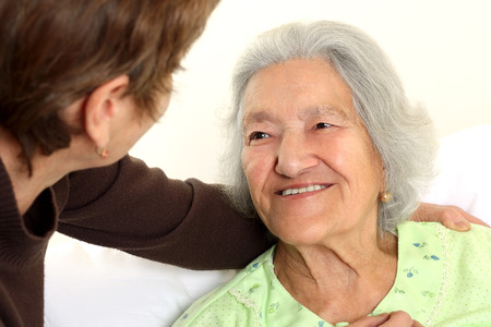home care nurse: Careing for a elderly woman lying in bed Stock Photo