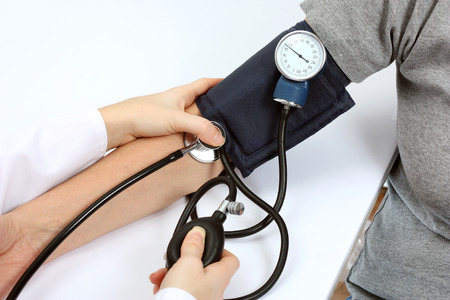 manual test equipment: Doctor checking blood pressure with stethoscope and sphygmomanometer