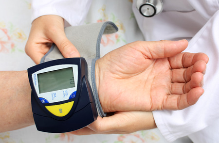 blood pressure gauge: Doctor checking blood pressure Stock Photo
