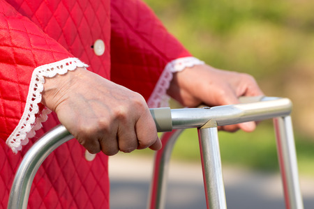aged person: Senior woman using a walker Stock Photo