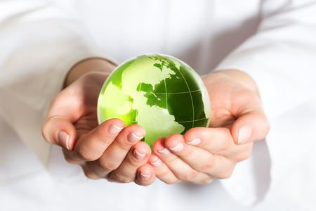Concepto de protección del medio ambiente con el globo de cristal en la mano