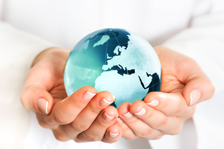 conquering: Hand holding blue earth globe Stock Photo