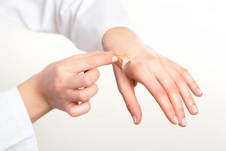 adhesive bandage: Hand putting adhesive bandage