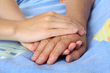 sick person: Hand touches and holds an old wrinkled hand Stock Photo