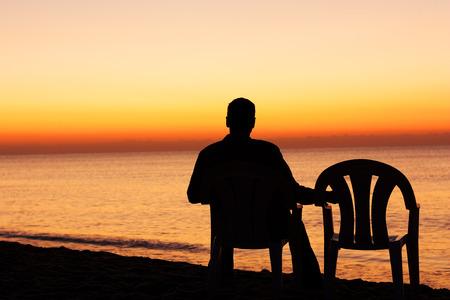 一人で椅子の上の男 写真素材