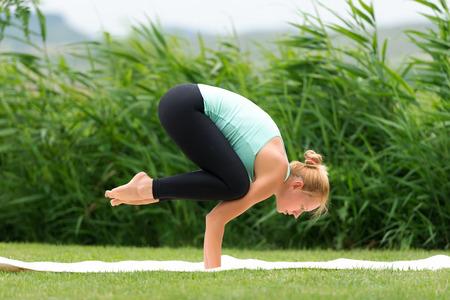 aerobic treatment: Woman making yoga crow pose