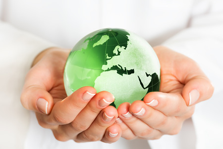 mundo manos: Mano que sostiene el globo de cristal verde