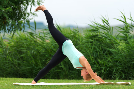 downward: Exercising downward facing dog yoga pose Stock Photo