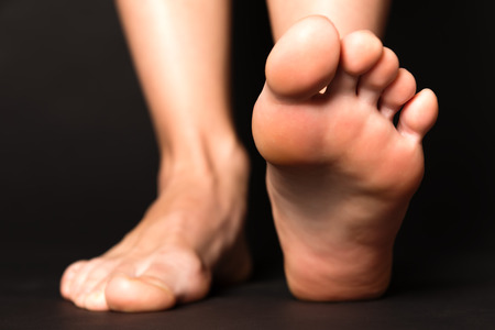bare women: Foot stapping isolated on black