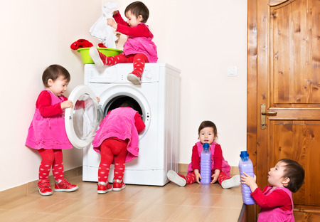 dirty clothes: Smiling cute little child using washing machine at home