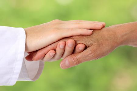 女性の手が自然にシニアを支援