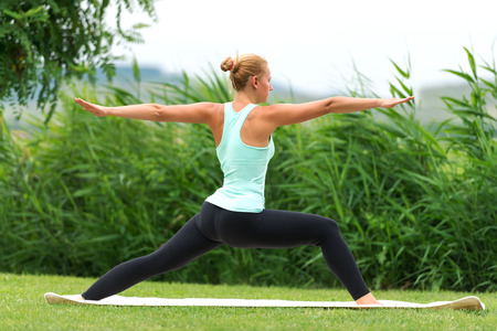 female warrior: Yoga virabhadrasana II warrior pose by woman