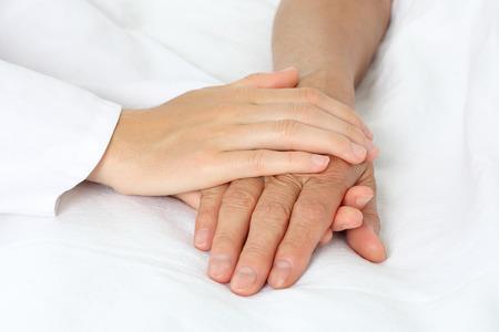 enfermera con paciente: La mano del paciente en la cama Foto de archivo
