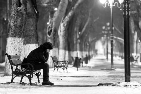 悲しい女性の冬時間にベンチに座っています。