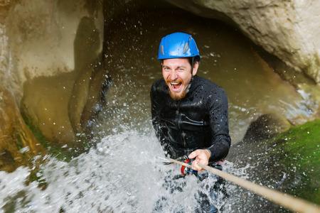Excité falaise homme d'escalade canyon avec une corde. Banque d'images