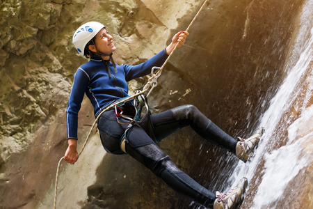 幸せな観光客がロープにぶら下がっている間崖を登るします。 写真素材