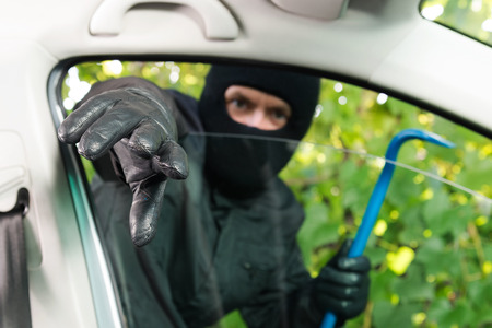 breaking in: Burglar breaking in a parking car with special tool.