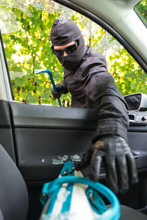 forceful: Robber breaking a cars windows to steal a woman bag. Stock Photo