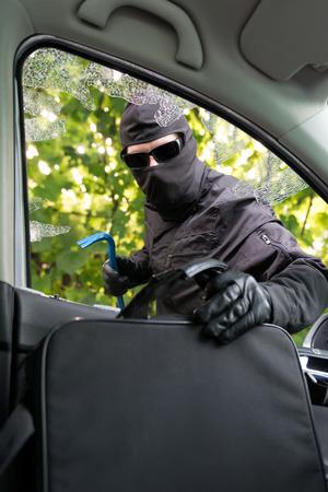 robo de autos: Antirrobo robando ordenador portátil de un coche cuyas ventanas se rompió con fuerza.