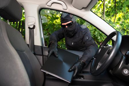 ladron: Antirrobo robando ordenador portátil de un coche cuyas ventanas se rompió con fuerza.