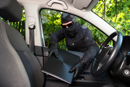 Burglar stealing laptop from a car whose windows he broke forcefully.