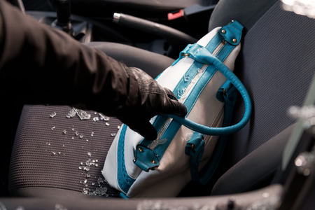 Robber breaking a cars windows to steal a woman bag. Stock Photo