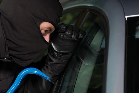 ladron: Ladrón preparándose para robar un coche de estacionamiento en la noche.