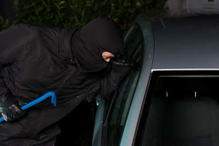 breakin: Thief preparing to steal a parking car at night. Stock Photo