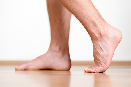 tiptoe: Pair of clean male feet without any illness making a step.
