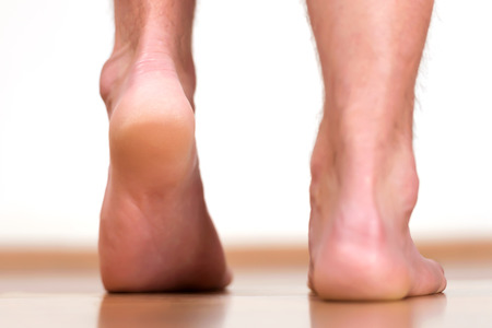 barefoot: Pair of male feet stepping - view from back. Stock Photo
