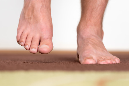 Stepping male feet feeling comfortable at home.