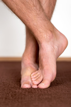 pies masculinos: Pies masculinos saludables sentirse cómodo en casa. Foto de archivo