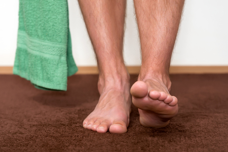 Healthy male feet with towel stepping towards the bathroom. Stock Photo