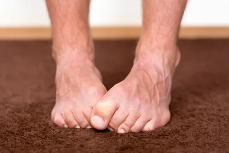 Pieds froids Itchy reposant sur le sol. Banque d'images