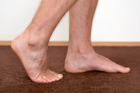 Healthy male feet feeling comfortable at home. Imagens