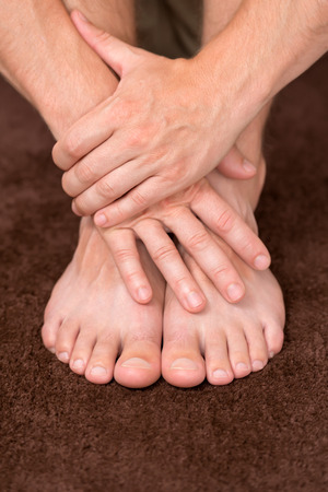 manos y pies: Manos masculinas que protegen par limpio y sano de los pies.