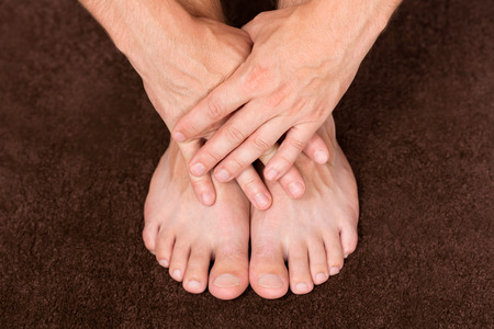 male parts: Male hands crossed over healthy resting feet.