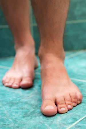 pies masculinos: Pies masculinos saludables que hacen un paso en el cuarto de baño.