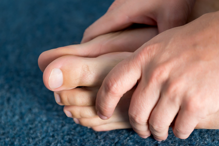foot fungus: Closeup view of hands and clean healthy feet.