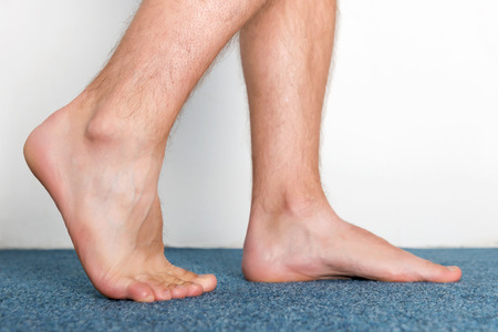 Healthy male feet making a step over home-like background. Standard-Bild