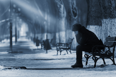 deprese: Sad žena sedící na lavičce v zimním období.