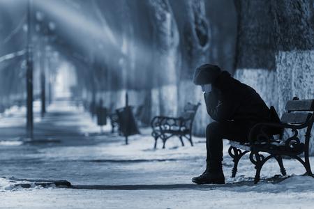 persona triste: Triste mujer sentada en un banco en el invierno. Foto de archivo