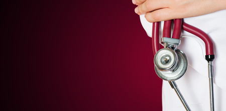 health care: Medical red background with a stethoscope Stock Photo