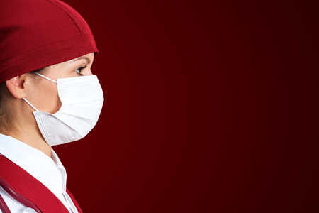 eye red: Female surgeon nurse in mask with red background
